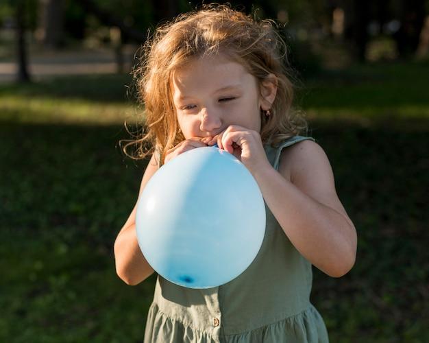 Mittleres schussmädchen, das luftballons aufbläst