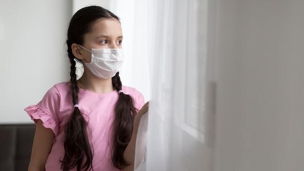 Mittleres schussmädchen, das medizinische maske trägt