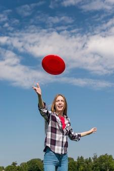 Mittleres schussmädchen, das mit frisbee spielt