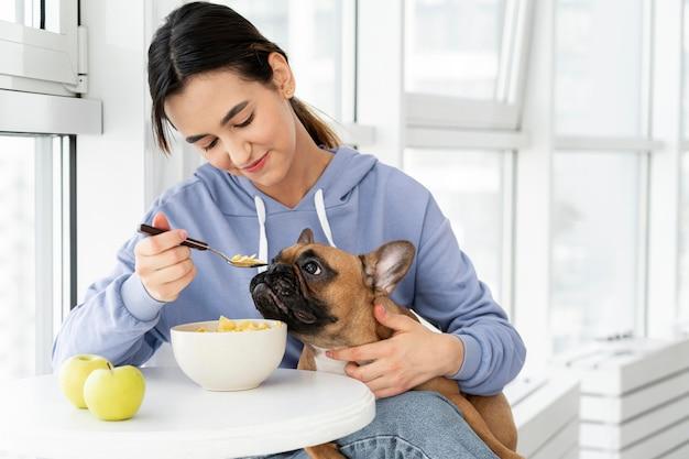 Mittleres schussmädchen, das mit hund isst