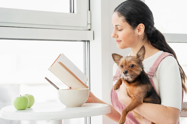 Mittleres schussmädchen, das mit hund liest