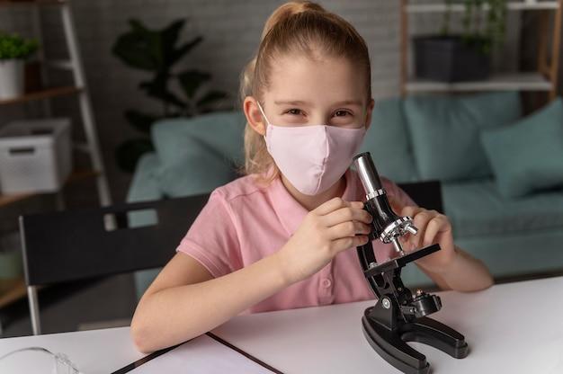 Mittleres schussmädchen, das mit mikroskop lernt