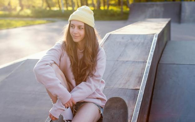 Mittleres schussmädchen, das mit skateboard sitzt