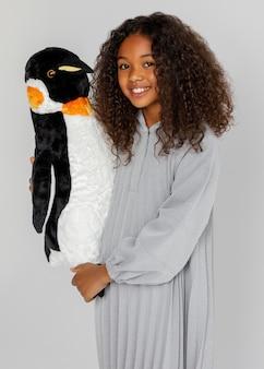 Mittleres schussmädchen, das pinguin hält