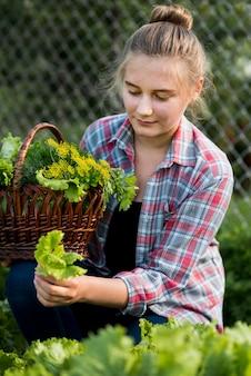 Mittleres schussmädchen, das salat aufnimmt