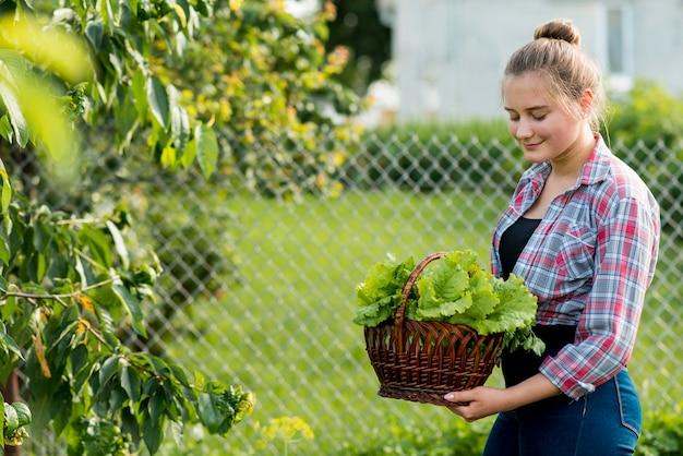 Mittleres schussmädchen, das salatkorb hält