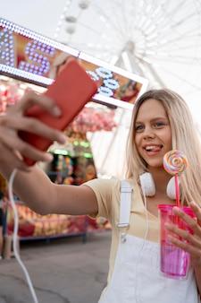 Mittleres schussmädchen, das selfie nimmt