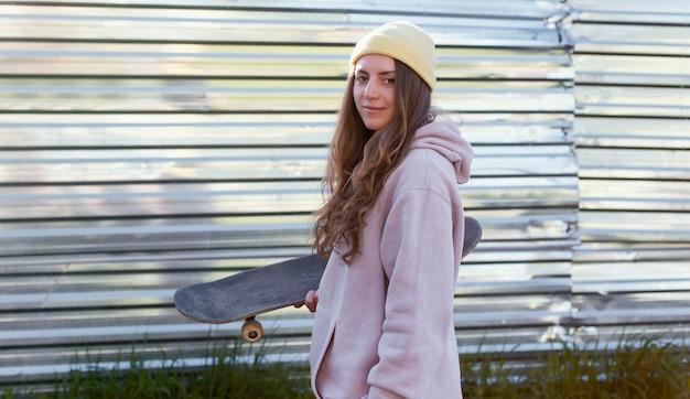 Mittleres schussmädchen, das skateboard hält