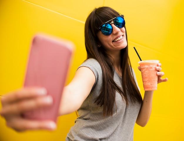 Mittleres schussmädchen mit dem getränk, das ein selfie nimmt