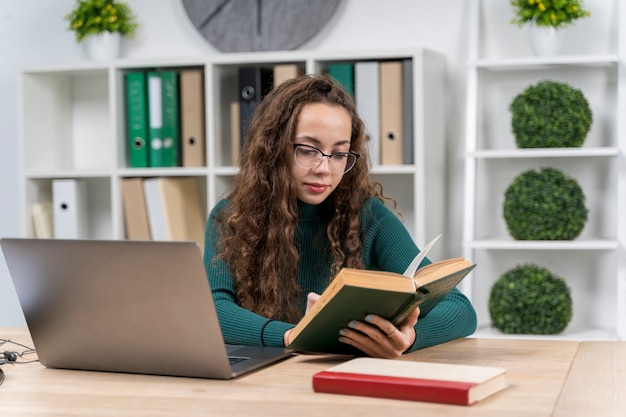 Mittleres schussmädchen mit gläsern zuhause studierend