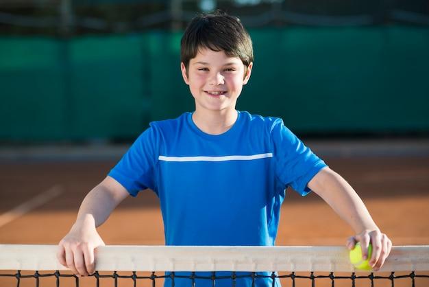 Mittleres schussporträt des kindes auf dem tennisfeld