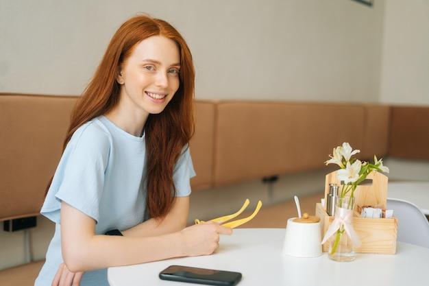 Mittleres schussporträt einer lächelnden attraktiven jungen frau, die in den händen gelbe stilvolle brillen hält, die am tisch im café sitzen und kamera betrachten. kaukasische dame der hübschen rothaarigen, die im gemütlichen café aufwirft.