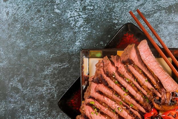 Mittleres seltenes rindfleisch geschnitten auf schwarzblech.