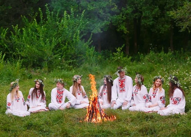 Mittsommer, junge menschen in slawischer kleidung sitzen im wald in der nähe des feuers.