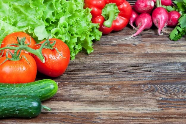 Mix aus frischem bio-gemüse auf braunem holztisch. salat, tomate, gurke, radieschen. hintergrund mit kopierraum