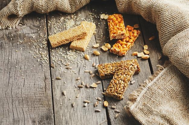 Mix von gozinaki riegel samen. leckere orientalische süßigkeiten aus den samen von sonnenblumen, sesam und erdnüssen, mit honig überzogen, mit glänzender glasur. makro-landhausstil