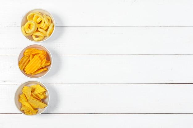 Mix von snacks: brezeln, cracker, pommes und nachos auf dem tisch
