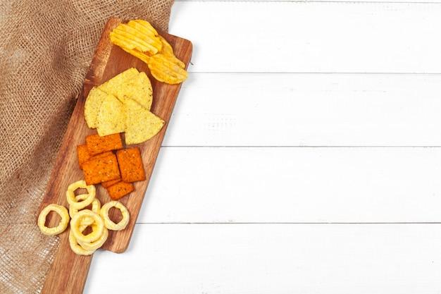 Mix von snacks mit brezeln, crackern, pommes und nachos auf dem tisch