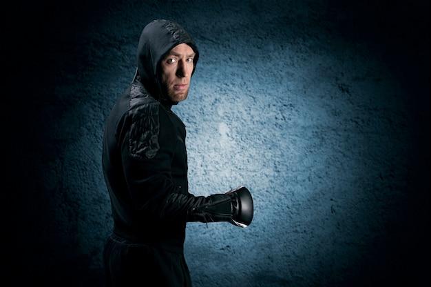 Mixed martial artist zieht im sweatshirt in die schlacht. konzept von mma, ufc, thailändisches boxen, klassisches boxen. gemischte medien