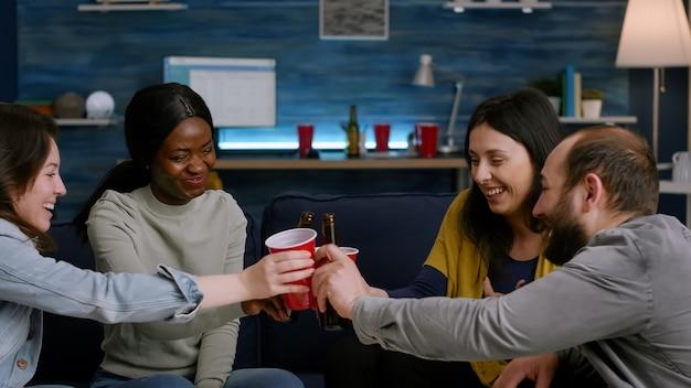 Mixed-race-freunde, die sich unterhalten, während sie spät nachts im wohnzimmer während der home-spaß-party herumhängen. gruppe gemischter menschen, die die zeit genießen, zusammen bierflaschen zuzujubeln
