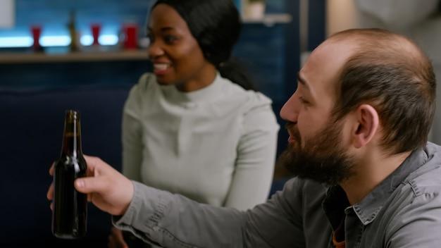 Mixed-race-freunde jubeln flaschen bier zu und verbringen zeit miteinander