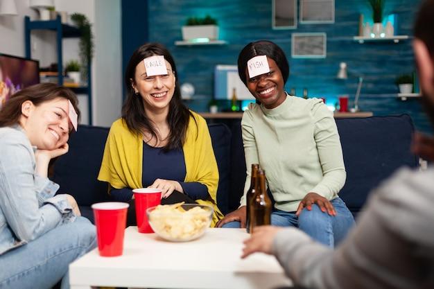 Mixed-race-freunde spielen raten, die mit klebrigen papieren auf der stirn spielen. gruppe von gemischtrassigen menschen, die spaß haben und zusammen lachen, während sie spät in der nacht auf dem sofa im wohnzimmer sitzen.