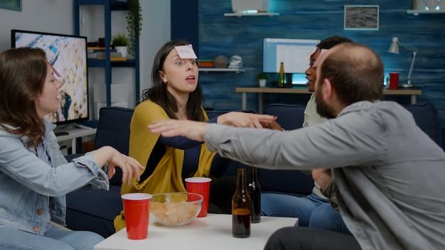 Mixed-race-freunde spielen raten, die mit klebrigen papieren auf der stirn spielen. gruppe von gemischtrassigen menschen, die spaß haben und zusammen lachen, während sie spät in der nacht auf dem sofa im wohnzimmer sitzen?