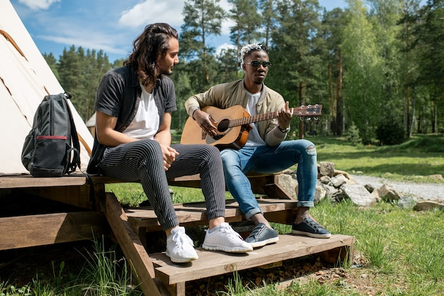 Mixed race kerl sitzt auf der veranda des zeltes und hört zu, wie schwarzer freund gitarre spielt