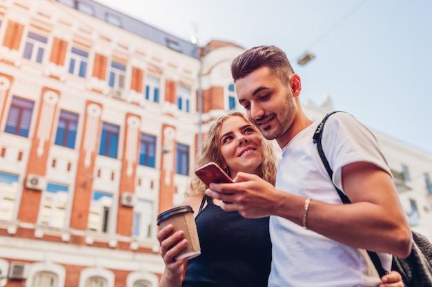 Mixed-race-paar in der liebe zu fuß in der stadt. arabischer mann und weiße frau trinken kaffee und benutzen smartphone im freien