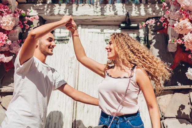 Mixed-race-paar in liebe tanzen auf der stadtstraße. junge leute, die spaß im freien haben. glücklicher mann und frau, die sich entspannen