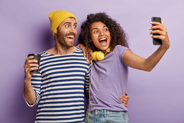 Mixed race schönes paar umarmen und stehen eng, posieren für selfie-porträt, haben fröhliche ausdrücke, trinken kaffee