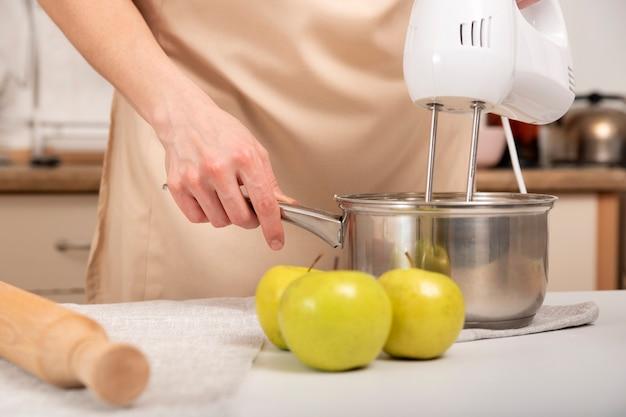 Mixer mischt die zutaten in einem topf. einen apfelkuchen kochen.