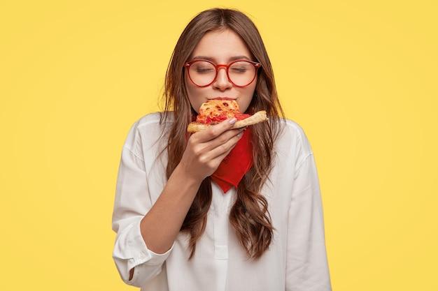 Mmm, so lecker! die dunkelhaarige hübsche frau isst ein stück italienische pizza, hält die augen vor vergnügen geschlossen, genießt den guten geschmack, trägt eine brille und ein hemd, isoliert über der gelben wand. esskonzept