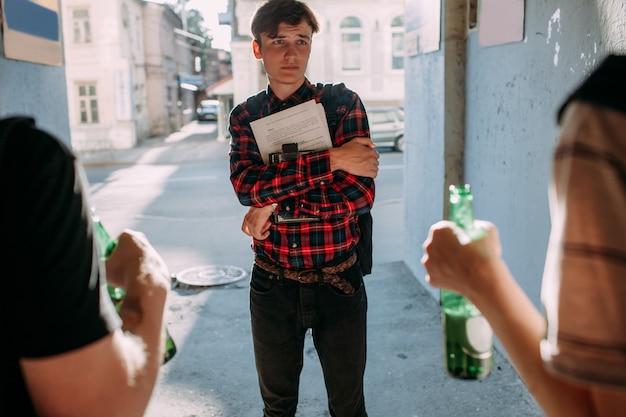 Mobbing bei jugendlichen. geek gegen straßengang. kluger junge hat angst vor jungen hooligans. konzept zur falschen zeit, falscher ort