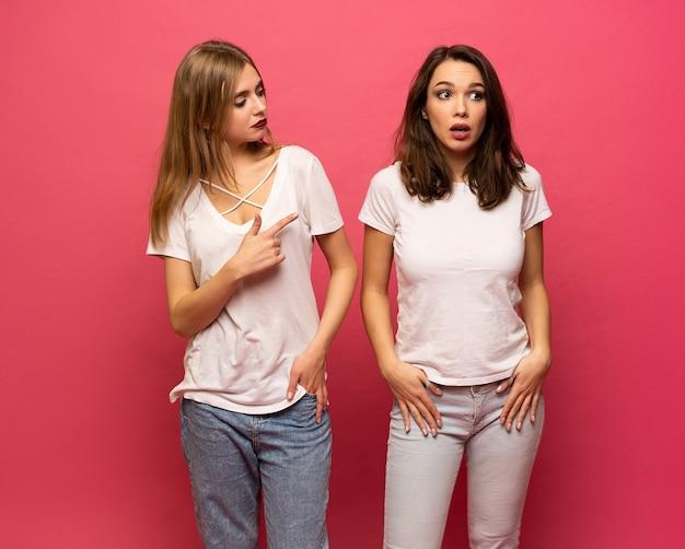 Mobbing, freundschaft und menschenkonzept - böse junge zwei damen, die über rosa hintergrund stehen, zwei teenager, die einen kampf haben