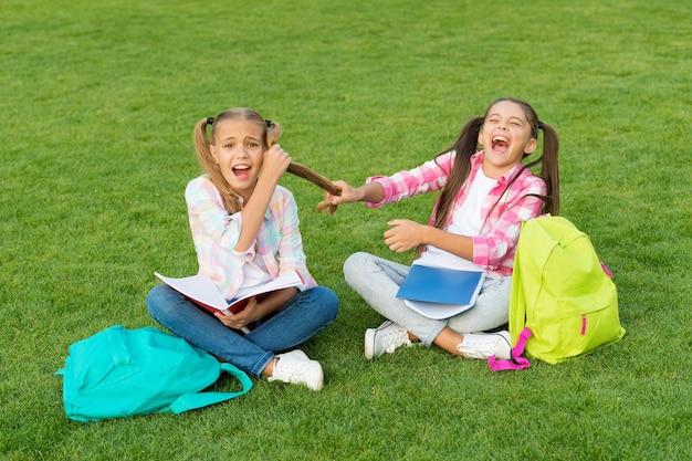 Mobbing in der schule. freizeit nach der schule verbringen. kleine kinderfreunde entspannen sich auf gras. zurück zur schule. literatur für mädchen. gemeinsam hausaufgaben machen. finde etwas interessantes im buch. notizen machen.