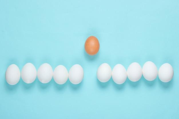 Mobbing-konzept mit eiern auf einem blauen tisch. draufsicht, minimalismus