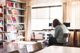Möbel in der Bibliothek mit arbeitender Person
