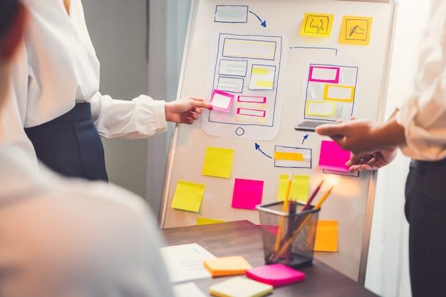 Mobile application designer entwickeln auf dem smartphone und rosa papier notiz zur hand, kreative skizzenplanung.