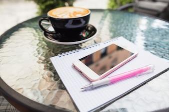 Mobile auf überprüftem Notizbuch und Stift mit Kaffee auf einer Tabelle im Freien