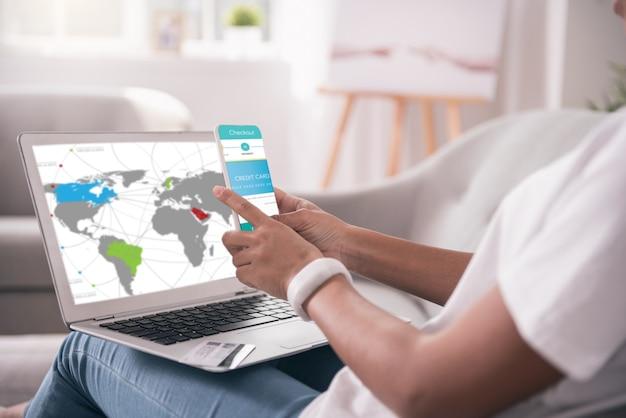 Mobile banking. nette kluge frau, die ihre smartphone-app benutzt, während sie eine zahlung mit ihrer kreditkarte macht