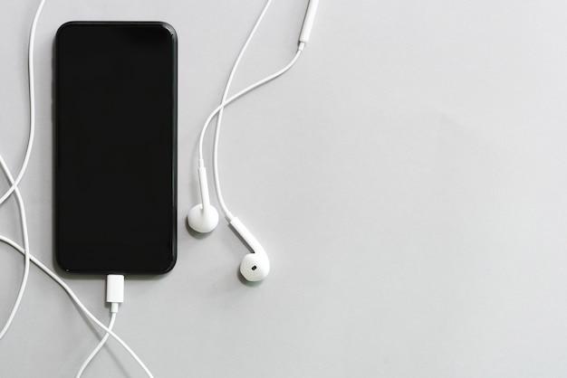 Mobile mit schwarzem bildschirm und kopfhörer auf weißer tabelle mit raum der freien kopie.