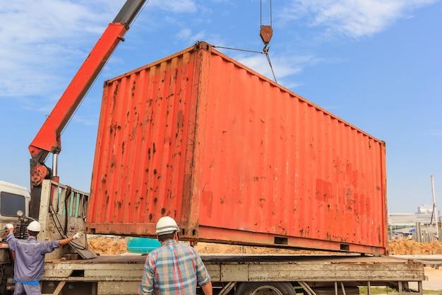 Mobiler kran im betrieb durch anheben und bewegen eines schweren bürocontainers