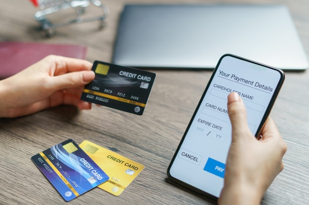 Mobiles bezahlen. hände mit smartphone und kreditkarte für online-einkäufe. (gefälschter bildschirm)