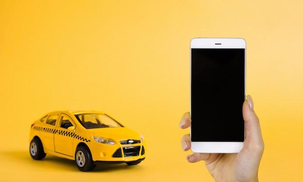 Mobiles online-anwendungskonzept für städtisches taxi. spielzeug gelbes taxi-automodell. hand, die smartphone mit taxiservice-app auf anzeige hält.