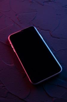 Mobiles smartphone auf dunkelroten blauen neonfarben. mock-up.perspektive ansicht. das layout des geräts. präsentation des interface-designs.