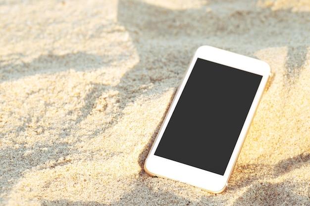 Mobiles smartphone legte tropfen auf tropischen sandstrand mit sonnenlichtbeschaffenheitshintergrund.
