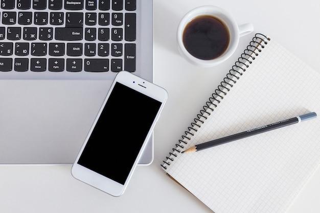 Mobiltelefon auf laptop mit tasse kaffee und bleistift über dem notizbuch