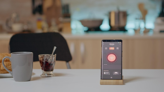 Mobiltelefon mit drahtloser beleuchtungsautomatisierungssoftware auf dem küchentisch in einem leeren haus mit intelligentem system, das licht einschaltet. smartphone mit high-tech-app zur steuerung der stromeffizienz