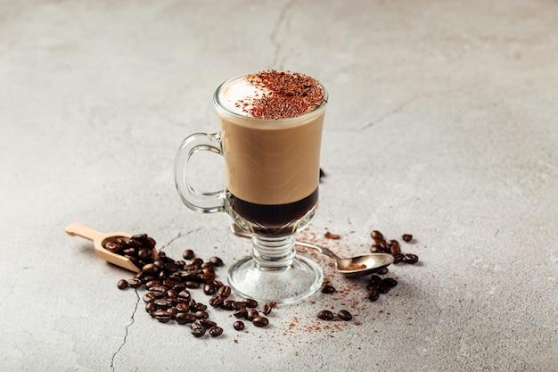 Mocaccino-kaffee in einem glasbecher auf dem grauen betonhintergrund, der mit bohnen verziert wird